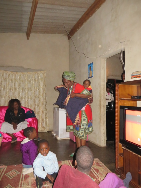 This woman invited me to her home. I asked how she was able to tie the baby on her back, so she demonstrated. 11 people lived here.