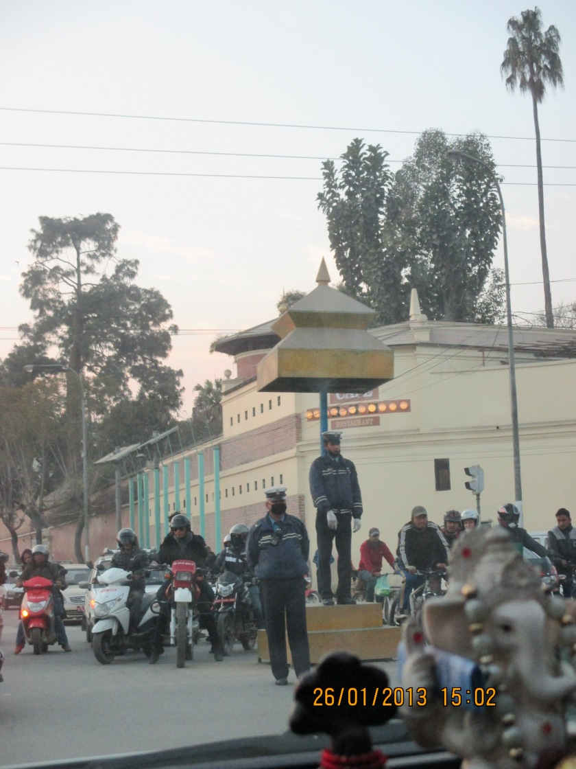 Traffic police stand on a pedestal in the middle of an intersection